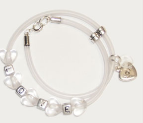 The letter L, O, V, and E are placed in between stunning color changing heart shaped beads with a heart charm with the words 'Love' inscribed.